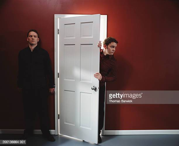 Two men, one standing against wall, other peering around door