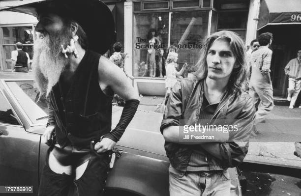 Two men one with a tap in his earlobe lean against a car in Greenwich Village New York City 1979