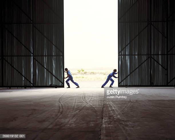 Two men opening warehouse doors