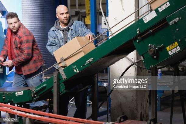 two men operating conveyor belt - unterschicht stereotypen stock-fotos und bilder