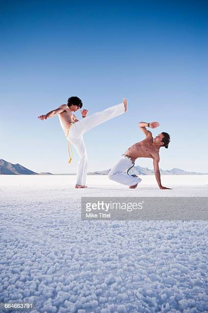 Two men opposite each other performing capoeira on Bonneville Salt Flats, Utah, USA
