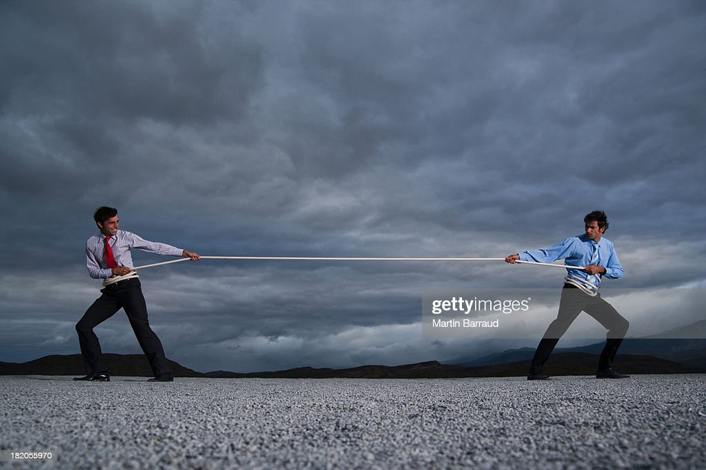Two men outdoors in tug of war : Stock Photo