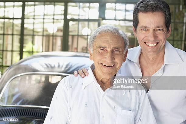 Dos hombres apoyarse en auto sonriendo al aire libre