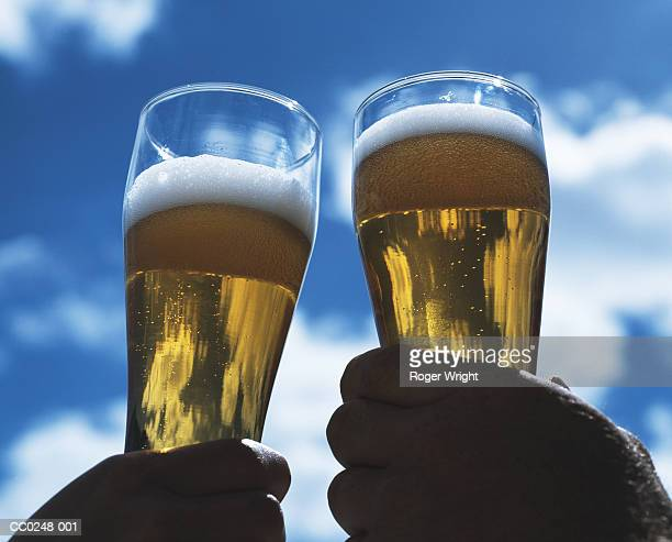 two men outdoors raising a toast with glasses of beer, close-up - honour stock pictures, royalty-free photos & images