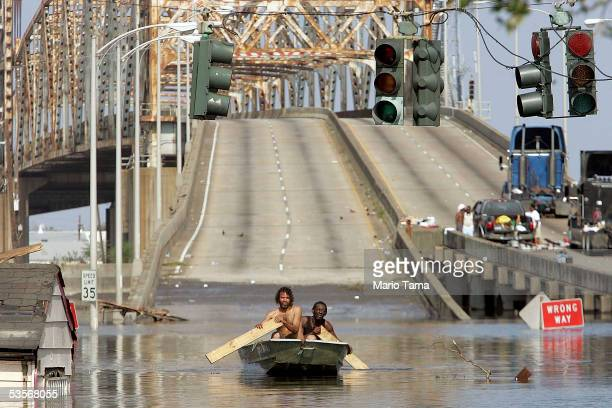 Two men paddle in high water after Hurricane Katrina devastated the area, August 31, 2005 in New Orleans, Louisiana. Devastation is widespread...