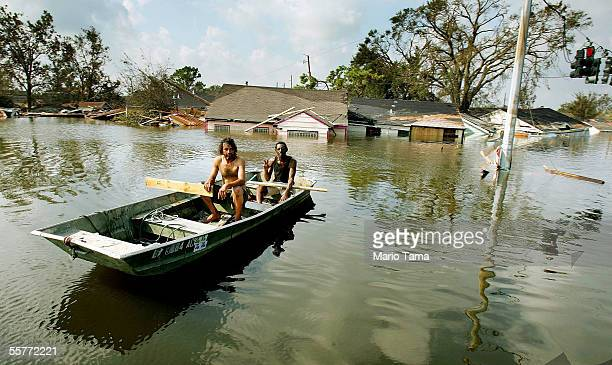 Two men paddle in high water in the Ninth Ward after Hurricane Katrina devastated the area August 31, 2005 in New Orleans, Louisiana. Devastation is...