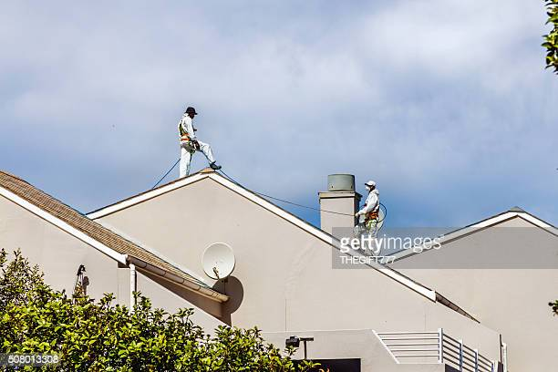 Two men painting a roof of a house