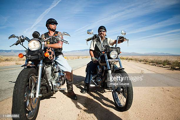 Two men parked on motorcycles at roadside