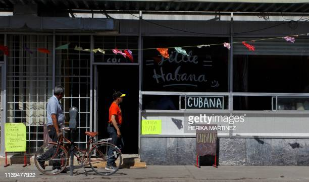 Two men pass by the Little Havana restaurant where a group of Cuban migrants work while waiting for their turn to cross to the United States to...