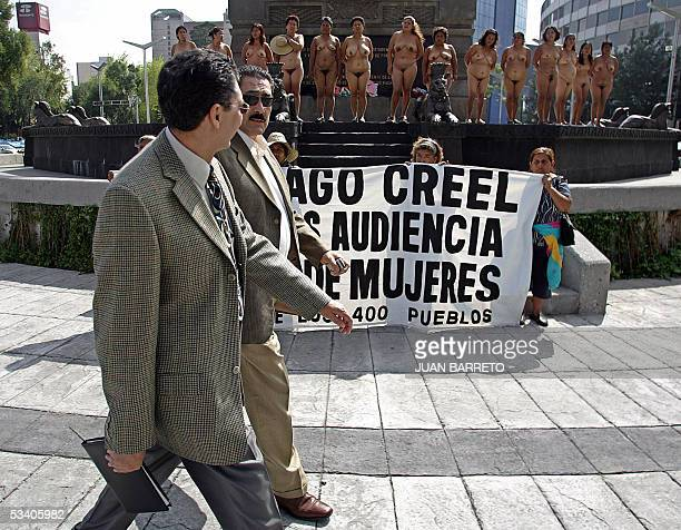 Two men pass in front of peasant women members of the 'Los 400 Pueblos ' group who demonstrate in the nude in Mexico City 18 August 2005 demanding...