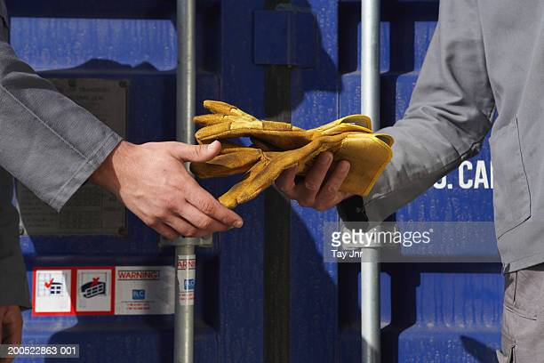 two men passing gloves beside cargo container, mid section - 手渡す ストックフォトと画像