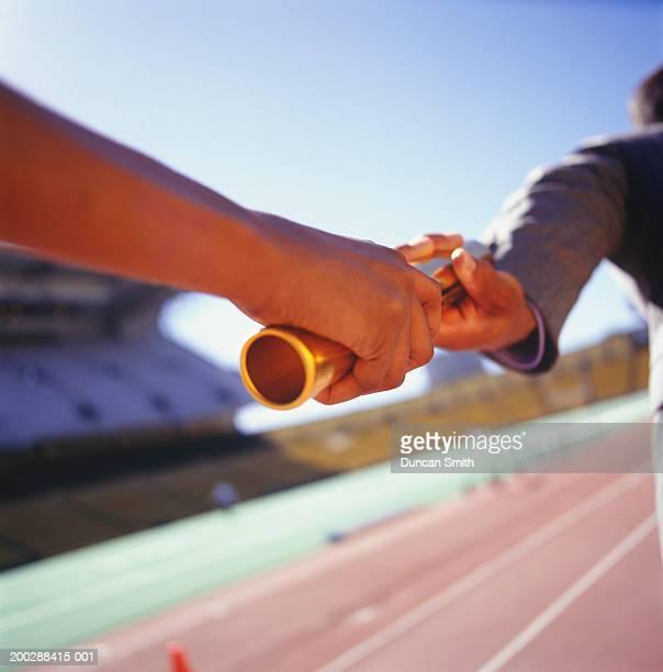 Two men passing golden baton in stadium, close-up