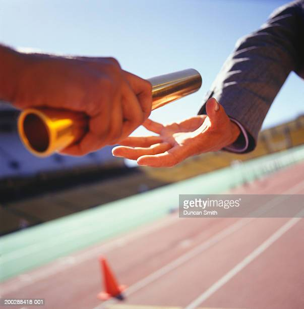 two men passing golden baton in stadium, close-up - relay baton stock photos and pictures