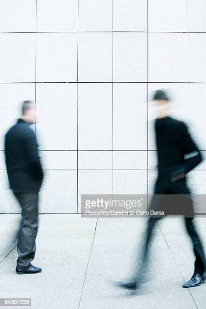 two men passing one another as they walk along the sidewalk - 通過する ストックフォトと画像
