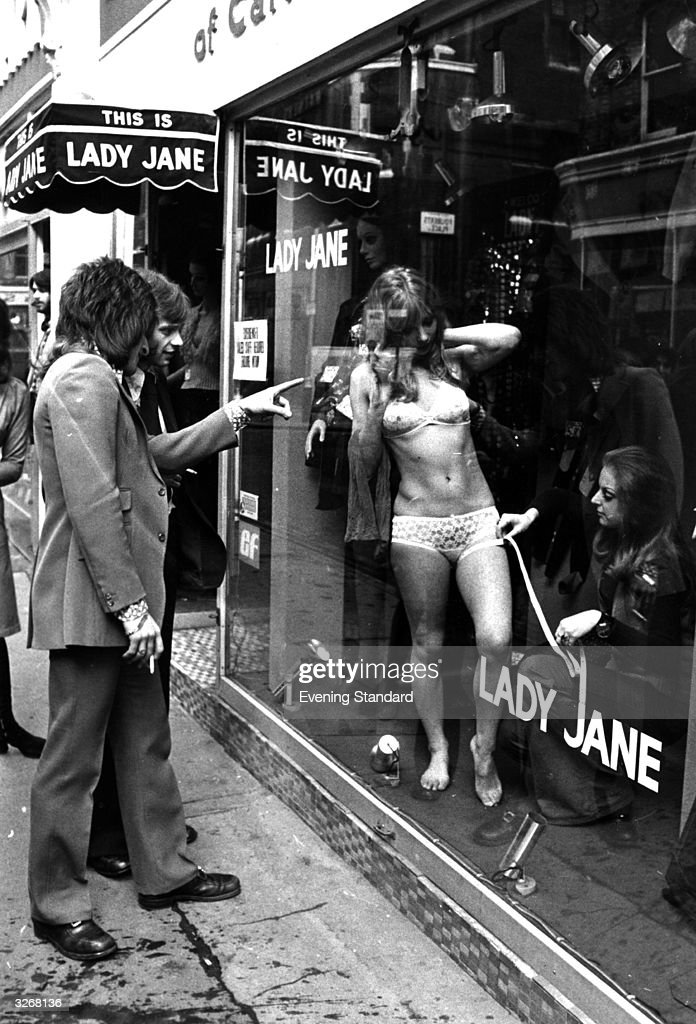 Two men peer through the window of the 'Lady Jane' shop in London's fashionable Carnaby Street to see a woman modelling underwear in the window display.