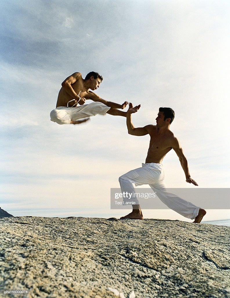 Two men performing martial arts on rocky ground, one in mid-air, full length : Stockfoto