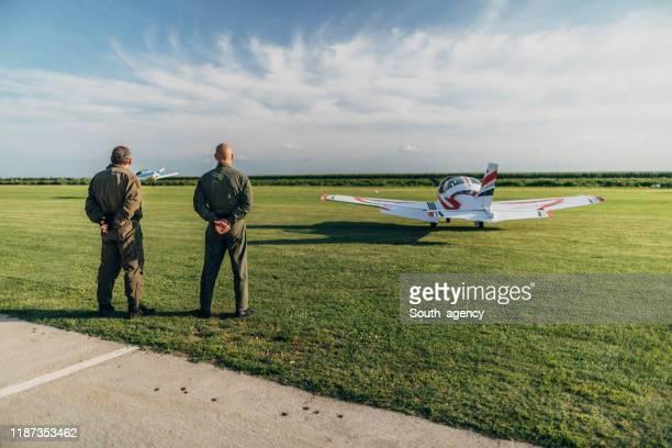 deux pilotes d'hommes restant près de l'avion d'hélice - combinaison de protection photos et images de collection