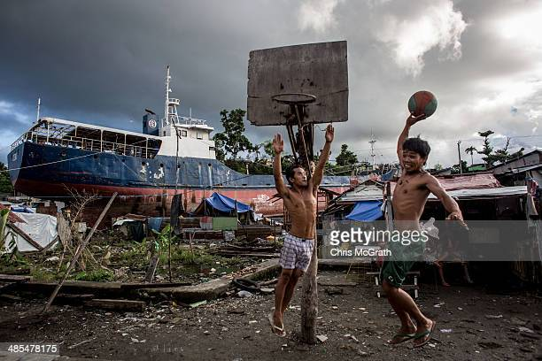 Two men play basketball on a makeshift court in a destroyed township on April 18 2014 in Tacloban Leyte Philippines People continue to rebuild their...