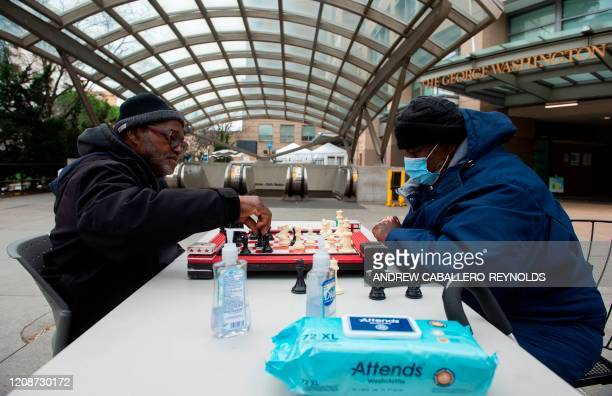 Two men play chess outside the George Washington University Hospital in Washington, DC on March 31, 2020. - To prevent the spread of coronavirus,...