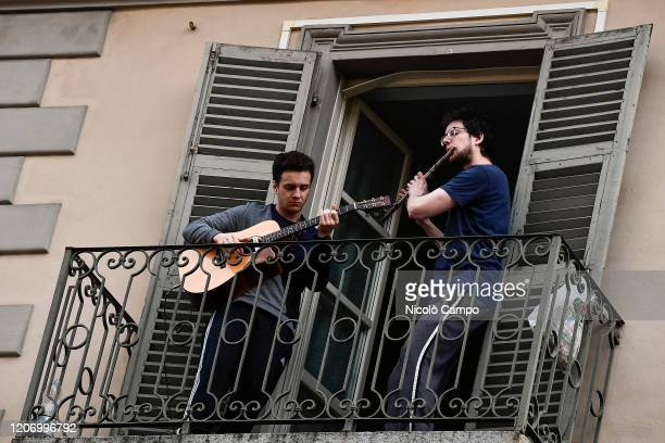 Two men play guitar and flute from the balcony of their home in the neighborhood San Salvario during a flash mob launched throughout Italy to bring...