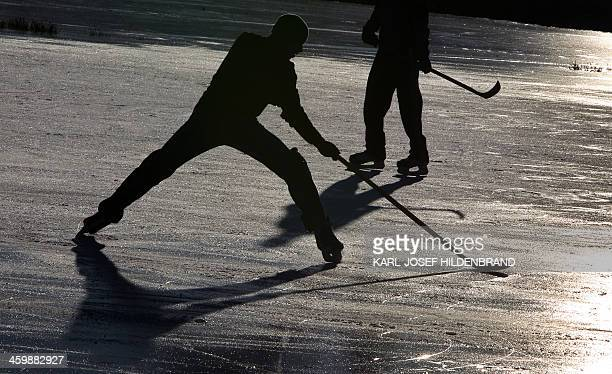 Two men play ice hockey on a frozen pond near Kaufbeuren southern Germany on December 31 2013 AFP PHOTO / DPA / KARLJOSEF HILDENBRAND / GERMANY OUT