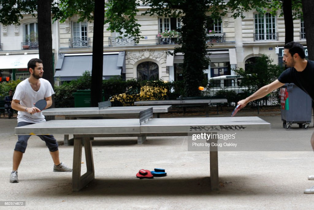 Two Men Play Ping Pong in Paris Park : Stock Photo