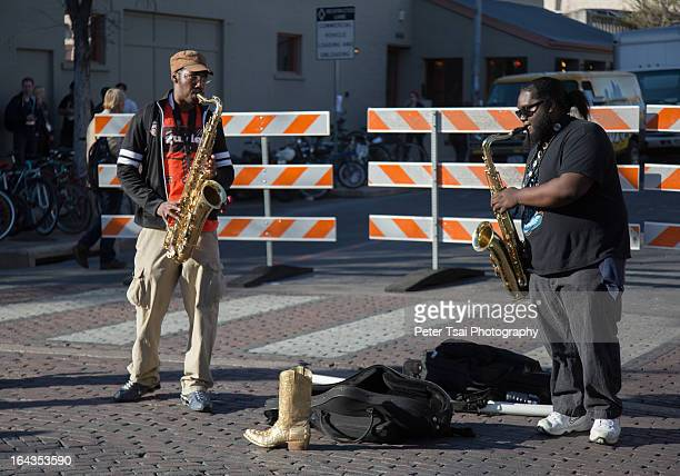 CONTENT] Two men play popular hits on saxophones on 6th Street in downtown Austin Texas during SXSW