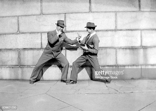 Two men playfully strike a boxing pose against a wall ca 1946