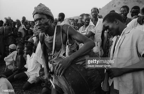 Two men playing a drum during a traditional wrestling match at Shawia village in the Nuba Mountains of Kordofan East Sudan 11th November 1995