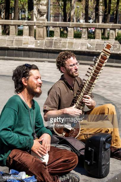 Two men playing a sitar and bongo on the street in Alameda Central