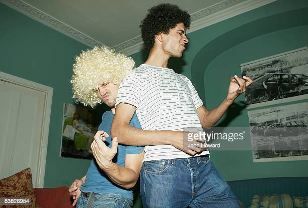 two men playing air guitar - male friendship stock pictures, royalty-free photos & images