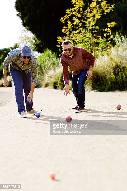 Two men playing bocci ball together in the park.