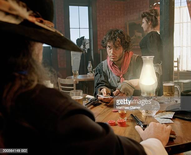 Two men playing cards at bar
