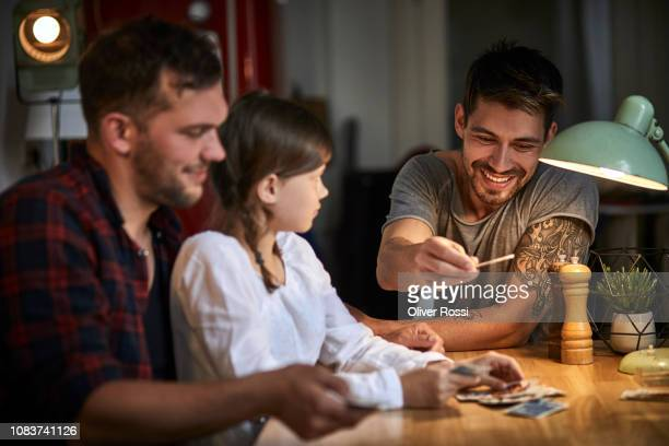 two men playing cards with girl at table at home - leisure games imagens e fotografias de stock