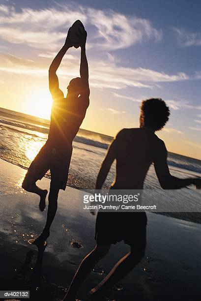 two men playing catch at a beach - only young men stock pictures, royalty-free photos & images