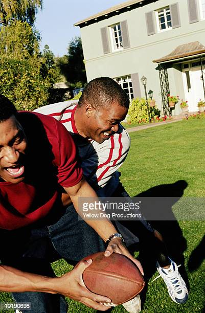 two men playing footbal outside home - tackling stock pictures, royalty-free photos & images