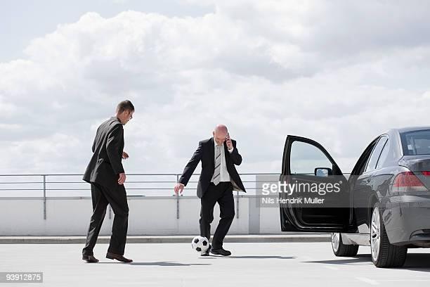 two men playing football near car