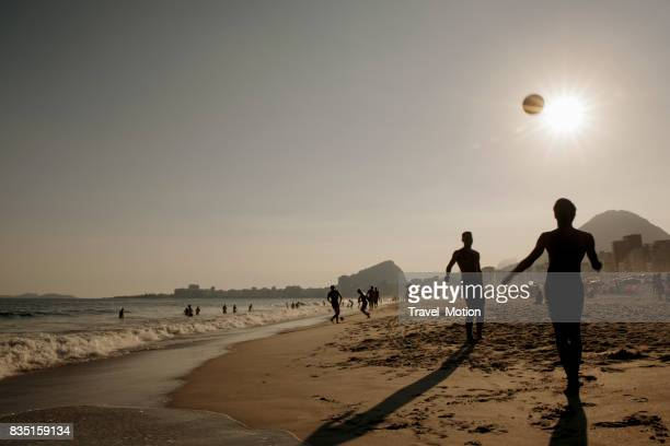 two men playing football on copacabana beach, rio de janeiro - famous footballers silhouette stock pictures, royalty-free photos & images