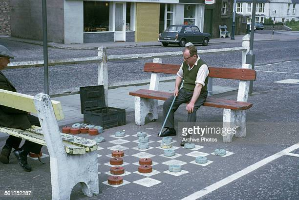 Two men playing giant draughts or checkers in Scotland UK circa 1965
