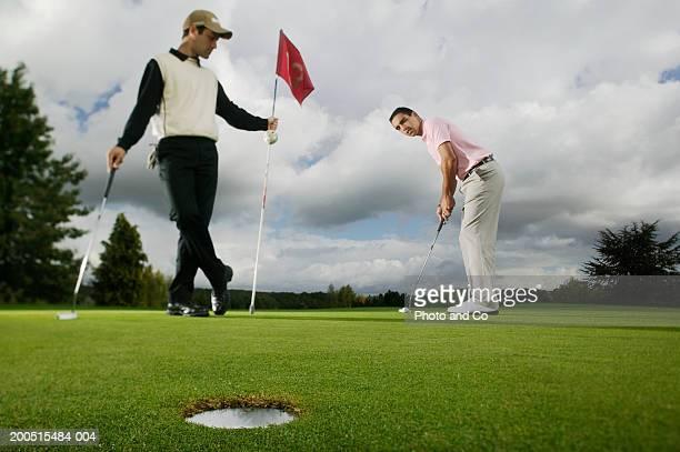 two men playing golf on course, one putting - putting - fotografias e filmes do acervo