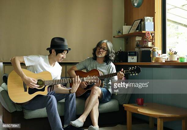 Two men playing guitar on sofa in living room