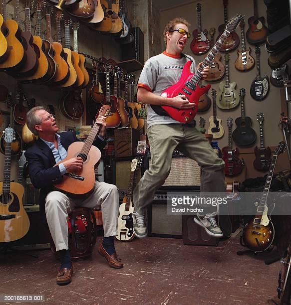 Two men playing guitars in guitar shop