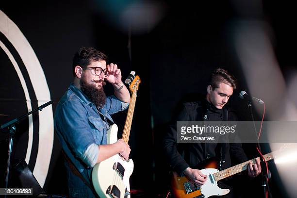 Two men playing guitars on stage