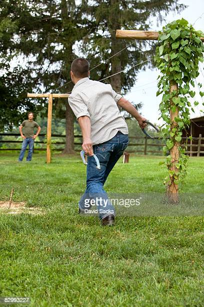 two men playing horseshoes - horseshoe stock pictures, royalty-free photos & images
