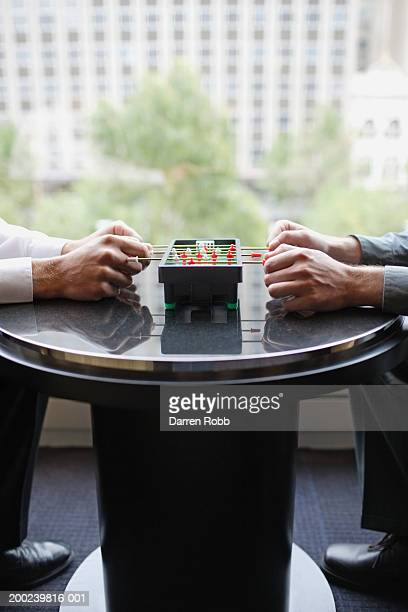 two men playing miniature table football, close-up - desk toy stock photos and pictures