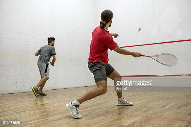 Two men playing racketball on a court.