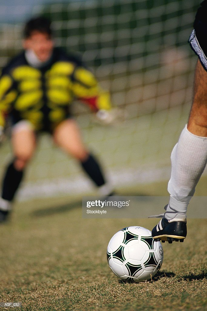 Two men playing soccer  goalie in background : Stock Photo