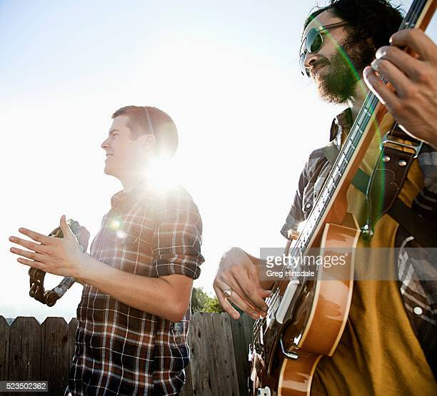 Two men playing tambourine and guitar