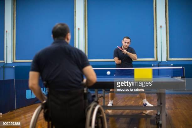 Deux hommes jouant ping pong uns contre les autres