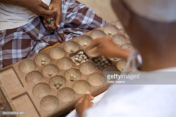 Two men playing wari board game, close-up